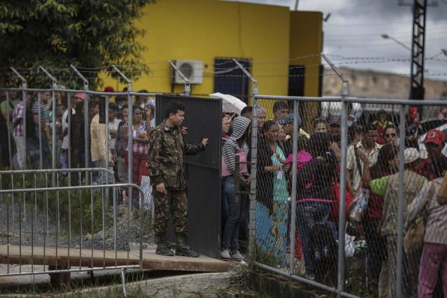 ACOMPAÑA CRÓNICA: VENEZUELA CRISIS - BRA09. PACARAIMA (BRASIL), 28/06/2018.- Centenas de inmigrantes venezolanos esperan para obtener autorización para ingresar a Brasil, en la sede de la aduana brasileña, en la Policía Federal de Pacaraima (Brasil) este 27 de junio de 2018. El Gobierno brasileño construirá un nuevo albergue para acoger a los cientos de venezolanos que han huido de la crisis económica, social y política de su país y que actualmente viven hacinados en las calles de Pacaraima, una pequeña ciudad en la frontera con Venezuela. El centro de acogida tendrá capacidad para 700 personas y recibirá a los inmigrantes más vulnerables que están retenidos en Pacaraima porque carecen de documentación necesaria para ingresar a Brasil o no tienen dinero para proseguir su camino. EFE/Antonio Lacerda