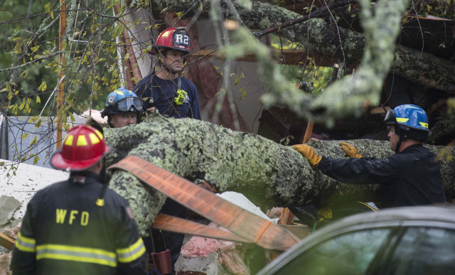 Firefighters work to remove a tree that fell on a house killing two residents during Hurricane Florence in Wilmington, North Carolina on September 14, 2018. A mother and her infant were killed when a tree fell on their house in Wilmington, North Carolina, the first reported fatalities from Hurricane Florence, police said Friday. Wilmington police tweeted that the father was transported to the hospital with unspecified injuries. Hurricane Florence made landfall near Wilmington on Friday morning, battering the coastal city with strong winds and torrential rain.  / AFP PHOTO / ANDREW CABALLERO-REYNOLDS