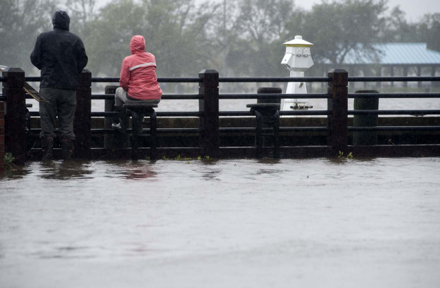 People watch rising flood waters on the Cape Fear River during Hurricane Florence in Wilmington, North Carolina on September 14, 2018. Florence smashed into the US East Coast Friday with howling winds, torrential rains and life-threatening storm surges as emergency crews scrambled to rescue hundreds of people stranded in their homes by flood waters. Forecasters warned of catastrophic flooding and other mayhem from the monster storm, which is only Category 1 but physically sprawling and dangerous. / AFP PHOTO / ANDREW CABALLERO-REYNOLDS