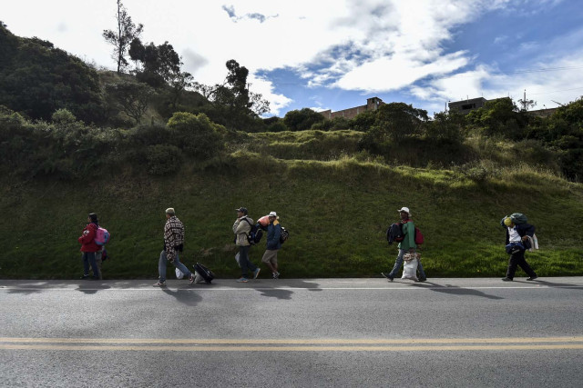 Members of Venezuelan migrant families Mendoza Landinez and Lomelly, walk along the Pan-American highway, between Pasto and Ipiales, Colombia, on their way to Peru, on August 23, 2018. On foot, by bus, on the backs of juddering trucks, like tens of thousands of others they slogged for days along the Pan-American highway through Colombia and Ecuador. Grubby and sleepless, their goal was to reach Peru, a sanctuary of sorts for a desperate Venezuelan family. Exhausted and swept by the endless wash of traffic noise on the highway's shoulder, the Mendoza Landinez family had the additional pressure of a deadline: to enter Peru before new rules required them to produce a passport.    / AFP PHOTO / Luis ROBAYO