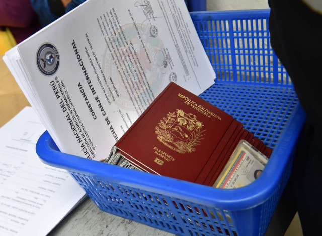 View of Venezuelan migrants documents at an Interpol facility in Lima on August 29, 2018.  Peru allowed the entry of hundreds of Venezuelan citizens as cooperation agreements between Colombia and Peru are drawn to filter migrants with criminal records, and health authorities at the Ecuador-Peru border evaluate how to deal with vast numbers of migrants not bearing health records. / AFP PHOTO / CRIS BOURONCLE