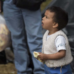 A Venezuelan migrant toddler, eats a sandwich at an improvised camp near the bus terminal in Bogota on September 11, 2018.  More than one hundred migrants set up a makeshift camp in a wooded area, near the bus terminal where they arrived, whether to stay in Colombia or to continue their journey. / AFP PHOTO / Raul ARBOLEDA