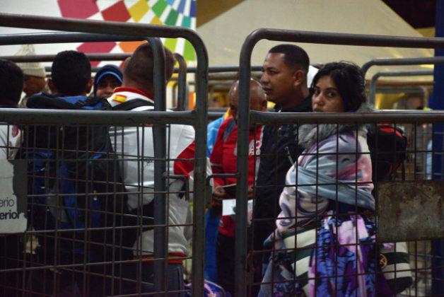 ECU02. TULCÁN (ECUADOR), 23/08/2018.- Emigrantes venezolanos esperan la llegada de uno de los autobuses que los trasladará a Perú hoy, jueves 23 de agosto de 2018, en Tulcán (Ecuador). Cientos de venezolanos se concentran esta noche en varios puntos de la ciudad ecuatoriana de Tulcán, en la frontera con Colombia, a la espera de una treintena de autobuses que, en principio, deben llegar a recogerles para trasladarlos a la frontera con Perú. Los migrantes están siendo clasificados en carpas por grado de vulnerabilidad, con el fin de dar prioridad a los de mayor edad, mujeres con niños, familias, etc. Según la acomodación de grupos en las carpas, el brazalete azul parece identificar a jóvenes y adultos que viajan sin familia. Los identificados con el rojo, en otras tres carpas de unas 50 personas cada una, que albergan familias con niños. EFE/Carlos Jiménez