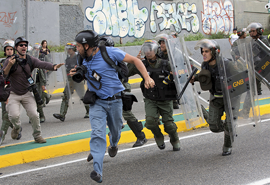 Reuters photojournalist Marco Bello runs as Venezuelan National Guard soldiers chase him during a protest outside the Supreme Court in Caracas, Venezuela, Friday, March 31, 2017. Security forces violently repressed small protests that broke out in Venezuela's capital Friday after the government-stacked Supreme Court gutted congress of its last vestiges of power, drawing widespread condemnation from foreign governments. (AP Photo/Ariana Cubillos)