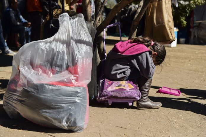 A Venezuelan migrant child is pictured at an improvised camp outside a bus station in northern Quito on August 22, 2018.  / AFP PHOTO / RODRIGO BUENDIA